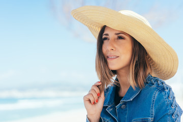 Thoughtful young woman in a wide-brimmed sunhat
