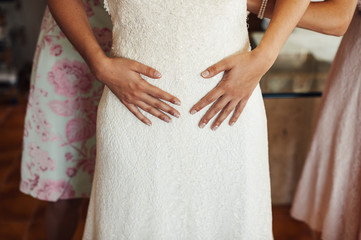 Bride getting dressed with hands in her hips