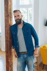 Bearded young man in casual faded jeans