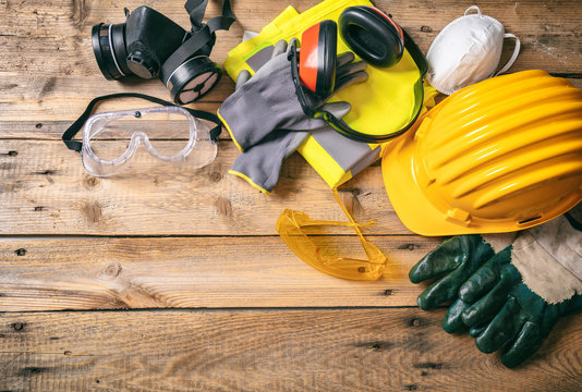Construction safety. Protective hard hat, headphones, gloves and glasses on wooden background, copy space, top view