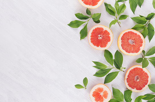Juicy half grapefruits and fresh green leaves as decorative spring pattern on white wood background, border.