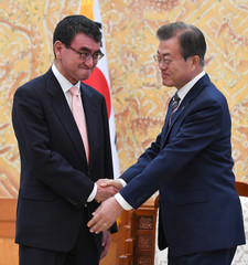 South Korean President Moon Jae-in shakes hands with Japanese Foreign Minister Taro Kono during their meeting at the presidential Blue House in Seoul