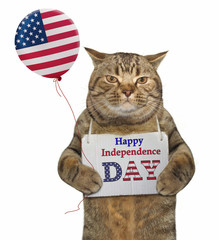 """The cat holds a balloon with a sign hanging around his neck. It says """" Happy independence day """"."""