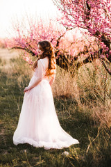 A girl in a beautiful dress strolls through a flowering garden