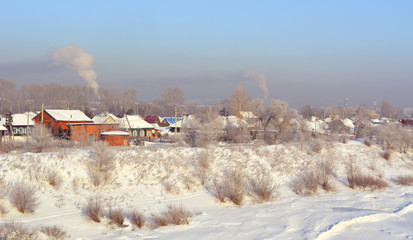 Winter landscape with village on the river bank.