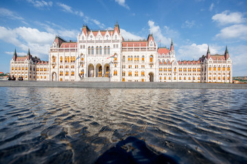 View on the main fasade of the famous Parliament building with reflection in the water during the morning light in Budapest, Hungary