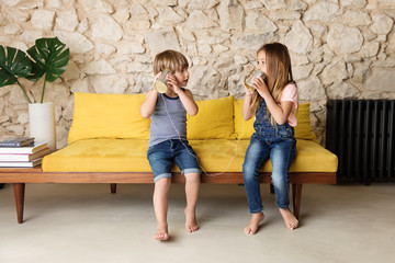 Siblings playing with tin can telephone on yellow sofa