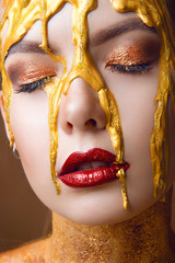 A glamorous portrait of a girl with professional make-up on closed eyes and spread gold paint on her face close-up.