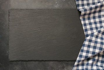 Black slate background with kitchen blue checkered towel. Cooking food, picnic or food background with copy space. Top view.