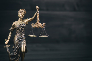 Scales of Justice, Justitia, Lady Justice on a black wooden background.