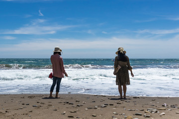Two women are standing on the beach and watching the sea waves, admiring the beautiful scenery
