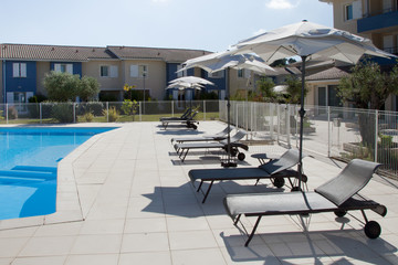 swimming pool in resort summer with chairs and umbrella