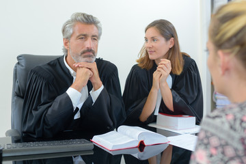 team of lawyers consulting client in office