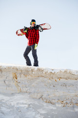 Picture of man with snowboard on shoulders standing on snowy mountainside