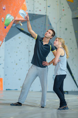 fit couple at the rock climbing wall at the gym