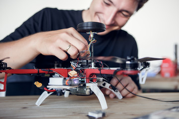 Image of young man cleaning quadrocopter at table