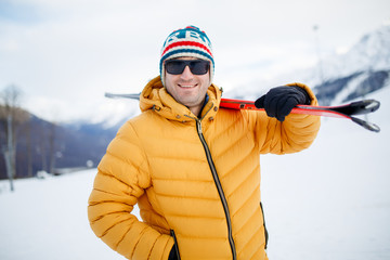 Portrait of sporty man with mountain skis