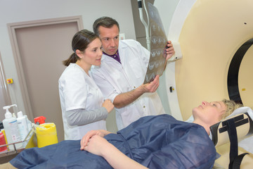 doctors checking xray image next to patient