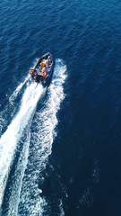 Aerial bird's eye view of inflatable rib boat cruising in high speed in turquoise clear water sea