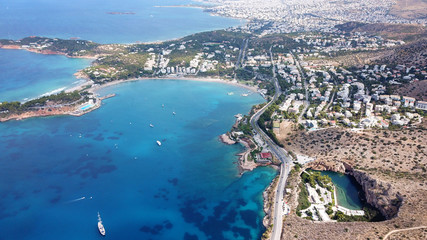 Aerial drone, bird's eye photo from iconic lake Vouliagmeni famous for healing abilities and Ateras Peninsula at the background, Athens riviera, Attica, Greece