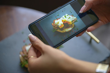 Photo of food on the smartphone. Sandwich with poached egg and bacon