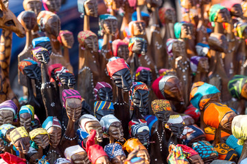 Wooden African figurines on display. The little figures have colourful headscarves.