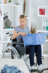 disabled woman on wheelchair putting towels into the washing machine