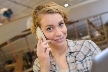 female artist smiling and talking on mobile phone in workshop
