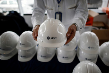 A man holds a work helmet with the logo of MSC during a visit at the STX shipyard site in Saint-Nazaire