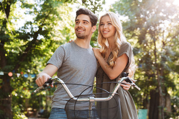 Picture of Happy lovely young couple standing together with bicycle