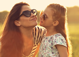 Happy fashion kid girl embracing her mother in trendy sunglasses and looking on nature background. Closeup toned portrait of happiness.