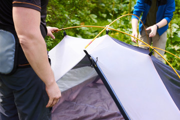 Camp in the tent - tourists setting a tent on the camping. Close up men's hands hold a tent while setting up a tent in the forest
