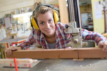 smiling female carpenter in her workshop