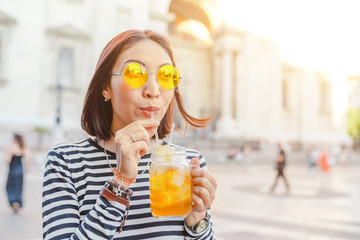 Happy female hipster student drinks a cool lemonade through a straw in a summer outdoor cafe