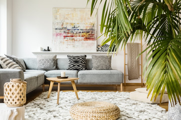 Pouf and wooden table in modern living room with painting above grey corner couch. Real photo Fotoväggar