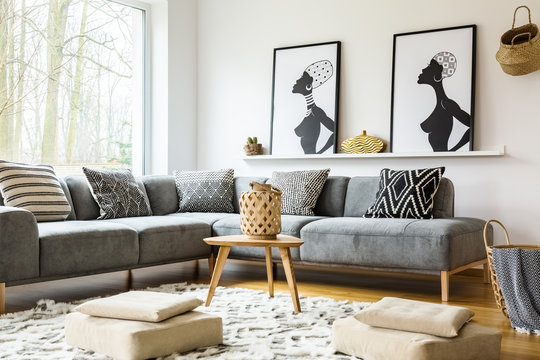 Poufs on carpet in bright african living room interior with grey corner sofa and posters. Real photo