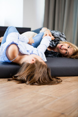 Cute teenage girl and her middle aged mother playing with each other while lying on the sofa