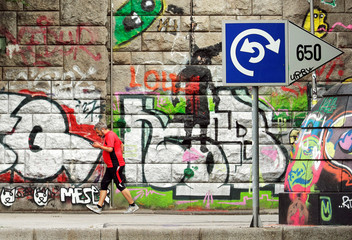 A jogger checks his mobile phone as he walks past Graffiti on the bank of Donaukanal channel in Vienna