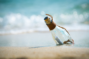 Letter message in a glass bottle on the beach , concept for communication.
