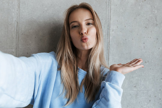 Happy pretty woman make selfie by camera blowing kisses.
