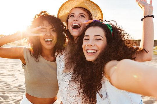 Three cheerful girls friends in summer clothes