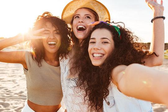Three cheerful girls friends in summer clothes