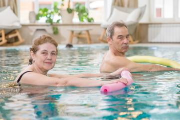 senior woman and man doing aqua fitness with swim noodles
