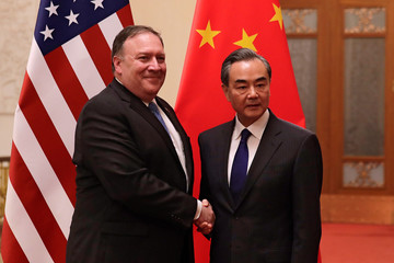 U.S. Secretary of State Mike Pompeo shakes hands with Chinese Foreign Minister Wang Yi as they pose for photographs at the Great Hall of the People in Beijing