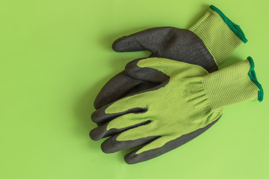 Rubber gloves for garden working on pastel color background top view. Copy space. Mockup for design.