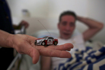 A nun holds a little toy car and the favourite toy of Emilio Ramos, a resident at the San Rafael nursing home in Arecibo