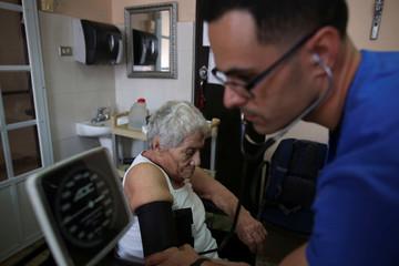 A nurse checks the blood pressure of John Rodriguez at the San Rafael nursing home in Arecibo