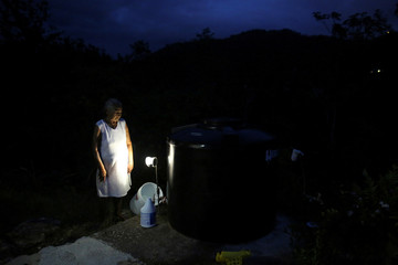 Ramona Olivera uses a solar lamp as she fills a bucket with water, as her neighbourhood is still without power nine months after Hurricanes Irma and Maria battered the island, in Adjuntas