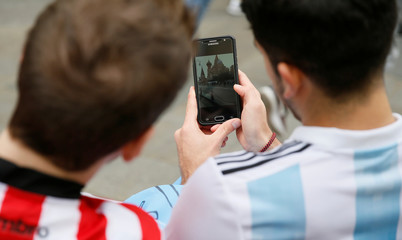 Soccer fans watch a photo of St. Basil's Cathedral on a mobile phone on the eve of the 2018 FIFA World Cup in central Moscow