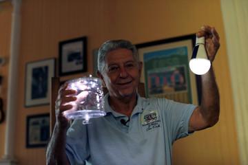 Alexis Massol, founder of Casa Pueblo, shows solar lamps used in the area, in Adjuntas